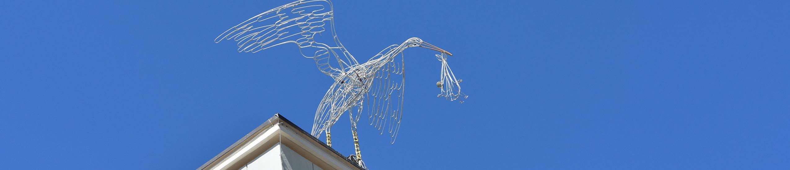 La statua della cicogna situata sul tetto del Comune